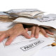 Close up of the hands of a man buried under a pile of bills and paperwork. There is a past due bill in the foreground. There is a clipping path.